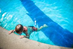 Activities on pool, boy swimming and playing in Stock Photos