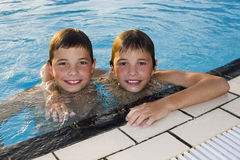 Activities on the pool. Boys swimming and playing in water Royalty Free Stock Photography