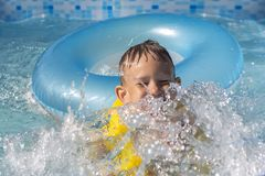 Activities on the pool, children swimming and playing in water, happiness and summertime. The Activities on the pool, children swimming and playing in water stock image