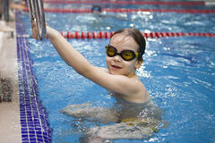 Activities on the pool. Cute boy swimming and playing in water in swimming pool Stock Images
