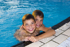 Activities on the pool. Cute boys swimming and playing in water Royalty Free Stock Photography