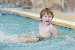 Activities on the pool, toddler boy swimming Stock Photos
