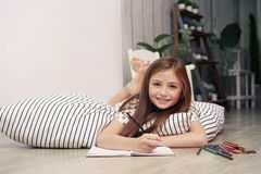Activities during school holiday, Little girl drawing on paper a. Nd lying on floor at home. Creative style concept royalty free stock image