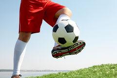 Activity. Horizontal image of soccer ball being kicked by footballer Stock Photo