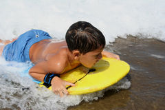 Activity. Child reaching the sand with his surfing board Royalty Free Stock Images