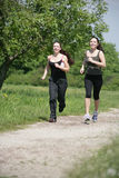 Activity. Two girls are jogging in the nature Stock Photo