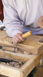 Activity craftsman carving wood in a medieval fair, carpentry to Royalty Free Stock Image