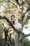 Activity, little girl climb tree in summer garden Stock Photo