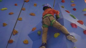 Activity of rock-climbing on artificial climbing walls, Caucasian boy in a harness climbing a wall with grips. Activity of rock-climbing on artificial climbing stock video footage