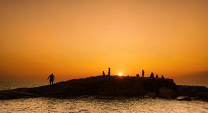 Activity on the stone Silhouette at sunset Royalty Free Stock Photo