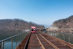 Activity trolley tram running on railway track. In river Royalty Free Stock Image