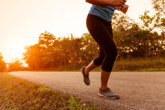 Activity woman run on rural road during sunset Royalty Free Stock Photo