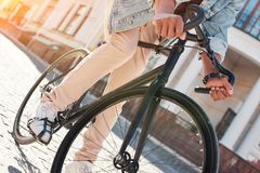 Activity. Young guy walking on city street riding bicycle close-up Stock Photo