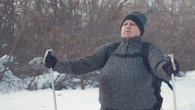 Activo una mujer mayor contratada a caminar nórdico con los palillos en el concepto sano de la forma de vida del bosque del invie almacen de video