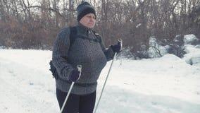 Activo una mujer mayor contratada a caminar nórdico con los palillos en el concepto sano de la forma de vida del bosque del invie almacen de metraje de vídeo