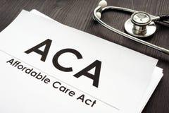Acto asequible ACA del cuidado y estetoscopio en un escritorio foto de archivo