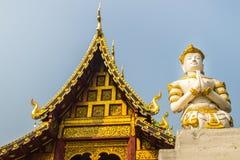 Acto blanco del ángel que paga respecto en la puerta de la entrada a la recepción en el templo budista público El ángel de oro de imágenes de archivo libres de regalías