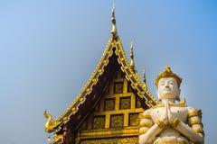 Acto blanco del ángel que paga respecto en la puerta de la entrada a la recepción en el templo budista público El ángel de oro de imagen de archivo libre de regalías