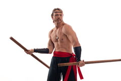 Actor Athlete man in trousers with naked torso practicing with wooden swords. On a white background royalty free stock photo