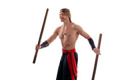 Actor Athlete man in trousers with naked torso practicing with wooden swords Royalty Free Stock Images