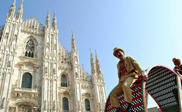 Actor descending tired a big show wheel during Carnival performance with Duomo in background. Royalty Free Stock Photography
