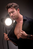 Actor in front of a light. Mid age actor with a cinema or studio light behind him Royalty Free Stock Photography
