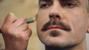 Actor is getting his makeup done before going on set, makeup artist at work stock footage