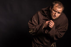 The actor in the guise of a beggar on a dark background Stock Photos
