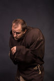 The actor in the guise of a beggar on a dark background Stock Image
