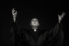 The actor in the guise of a priest against a dark background Royalty Free Stock Photo