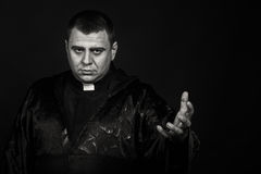 The actor in the guise of a priest against a dark background Stock Photo