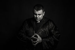 The actor in the guise of a priest against a dark background Stock Photography
