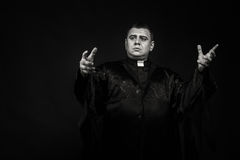 The actor in the guise of a priest against a dark background Stock Images