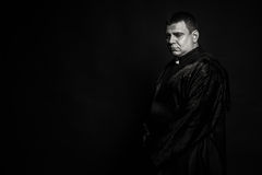 The actor in the guise of a priest against a dark background Royalty Free Stock Photography