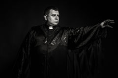 The actor in the guise of a priest against a dark background Royalty Free Stock Images