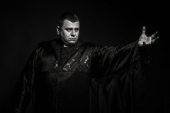 The actor in the guise of a priest against a dark background Stock Image