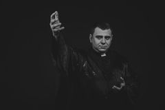 The actor in the guise of a priest against a dark background. Professional makeup. Beautiful costumes and accessories. Photos for magazines, posters and Royalty Free Stock Images