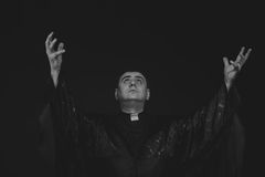The actor in the guise of a priest against a dark background. Professional makeup. Beautiful costumes and accessories. Photos for magazines, posters and Stock Photos