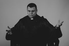 The actor in the guise of a priest against a dark background. Professional makeup. Beautiful costumes and accessories. Photos for magazines, posters and Royalty Free Stock Image