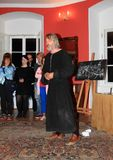 Actor in historical costume of monk. Standing in front of small blackboard with drawing of changes on castle at Night performance on castle Houska, Czech Royalty Free Stock Image