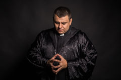 Actor in the image of the priest on a dark background Stock Photography