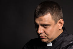Actor in the image of the priest on a dark background Royalty Free Stock Photos