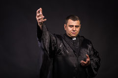 Actor in the image of the priest on a dark background Stock Image