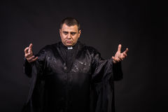 Actor in the image of the priest on a dark background Royalty Free Stock Photography