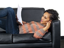 Actor lying and reading a script. Young African American female actor lying and reading a script Stock Photo