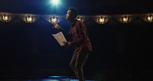 Actor performing a monologue in a theater. Medium close-up shot of an actor performing a monologue in a theater while holding his script stock images