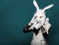 Actor posing in white rabbit suit with earphones Stock Photography