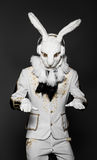 Actor posing in white rabbit suit with earphones. On  black background Stock Image