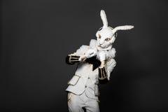 Actor posing in white rabbit suit with earphones Stock Photo