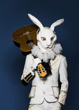 Actor posing in white rabbit suit playing guitar Stock Photos